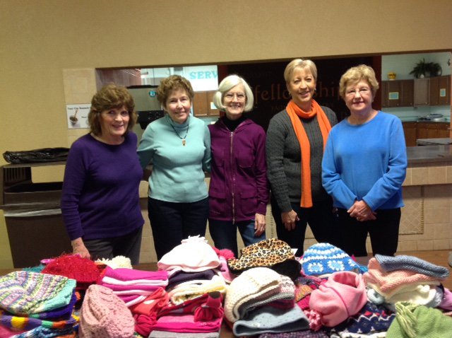 Five women standing behind a table filled with donated hats and mittens.